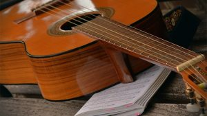Guitar with a book. Best Guitar Books Featured Image.